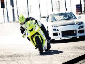 Moto seguida por un coche de drift