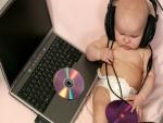 Bebé escuchando música en un ordenador portátil