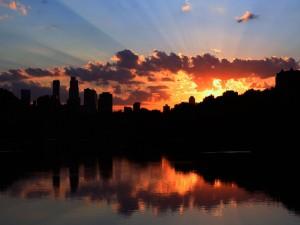 El sol del amanecer tras los edificios de una ciudad