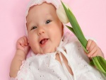 El bebé de la sonrisa sosteniendo un tulipán