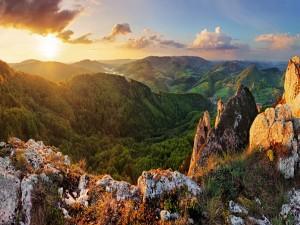 El sol se va asomando iluminando montañas y bosques