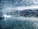 Barca alejándose de un iceberg