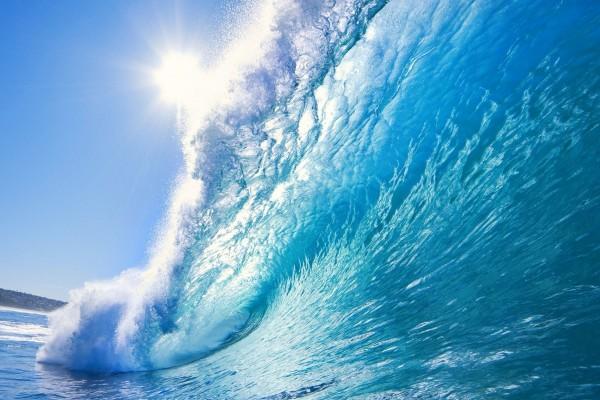Sol iluminando una gran ola