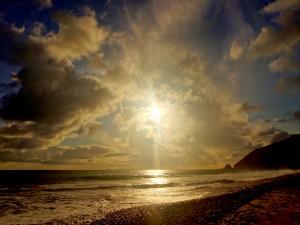 Sol brillando sobre una playa pedregosa