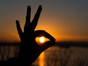 Sol entre los dedos de una mano