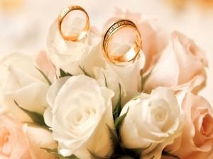 Anillos de boda sobre un ramo de rosa blancas