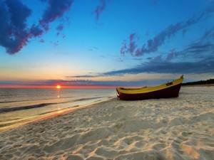 Barca en la playa al amanecer