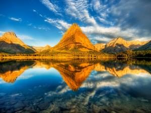 Sol iluminando las montañas y el lago