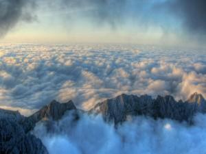 Picos montañosos sobresaliendo del mar de nubes