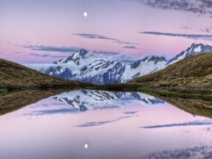 Luna y montañas reflejadas en un lago