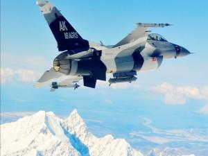 F-16 volando sobre montañas nevadas