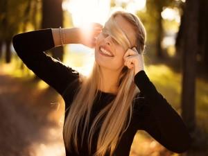 Hermosa mujer tapándose los ojos con un mechón de cabello rubio