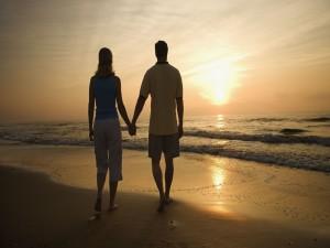 Pareja de enamorados caminando por la playa