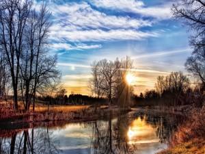 Sol del amanecer reflejado en el río