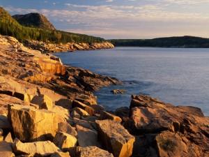 Sol iluminando las rocas de la orilla