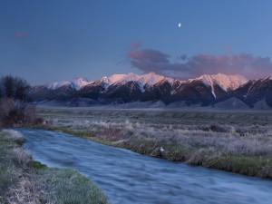 Luna sobre las montañas vista desde la orilla de un río