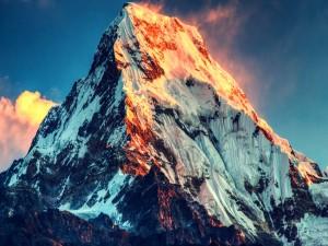 Sol iluminando la cima de una gran montaña
