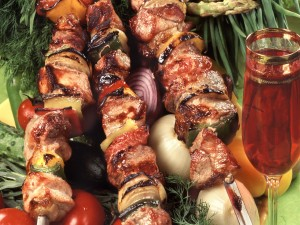 Brochetas de carne con verduras y una copa de vino