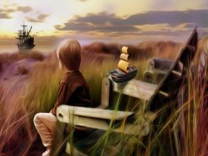 Niño sentado mirando a un navio en el mar