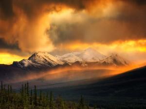 Nubes iluminadas por el sol entre las grandes montañas