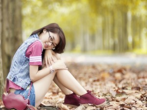 Chica sentada sobre hojas otoñales