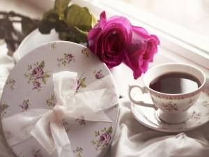 Dos rosas junto a una taza de té