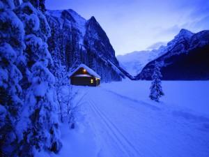 Casa iluminada en un paraje cubierto de nieve