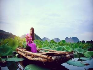 Mujer sentada en un bote sosteniendo flores de loto