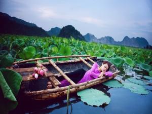 Chica durmiendo en un bote entre flores de loto