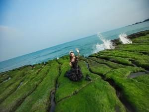 Chica en unas rocas cubiertas de musgo