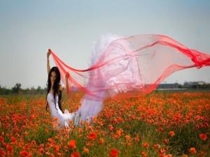Mujer con vestido blanco en un campo de amapolas