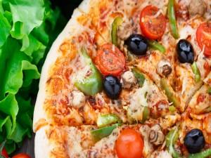 Exquisita pizza con aceitunas negras, tomates cherry, pimientos y queso
