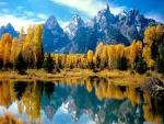 Montañas y árboles otoñales reflejados en el lago