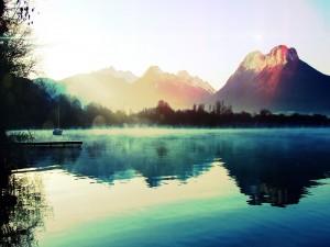 Sol iluminando el lago y las montañas