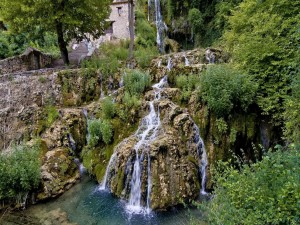 Cascada junto a una casa de piedra