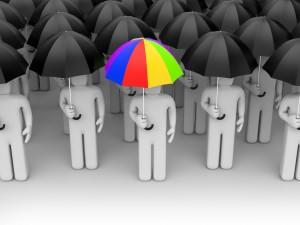 Un paraguas de colores entre varios de color negro