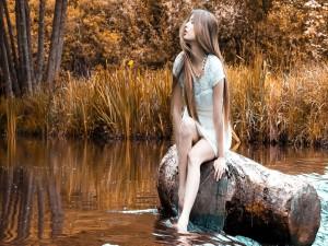 Hermosa mujer sentada en un tronco en el río