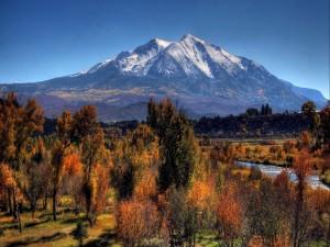 Río fluyendo en otoño bajo la montaña