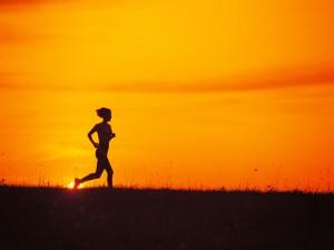 Mujer practicando running a la salida del sol