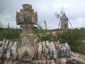Molino de viento junto a una cruz de piedra