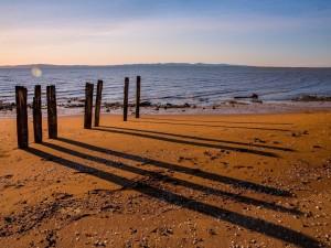 La sombra de unos pilares de madera sobre la playa arenosa