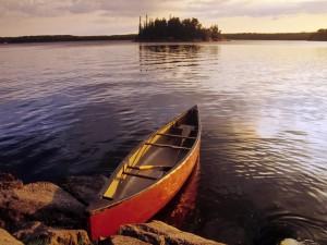 Canoa de madera en la orilla del lago