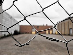 Verja rota en un recinto industrial