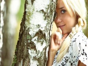 Bella chica rubia junto al tronco de un árbol