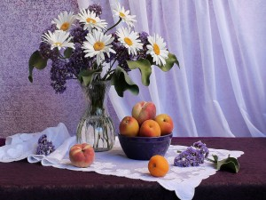 Jarrón con lilas y margaritas junto a unos melocotones
