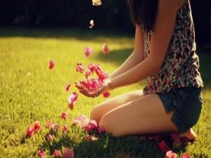 Muchacha jugando con pequeñas flores rosas