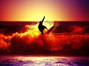 Un hombre practicando surf en la puesta del sol