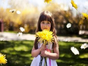 Hermosa niña sosteniendo una flor