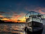 Barco junto al muelle en el ocaso del sol