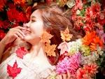 Chica feliz entre flores y hojas